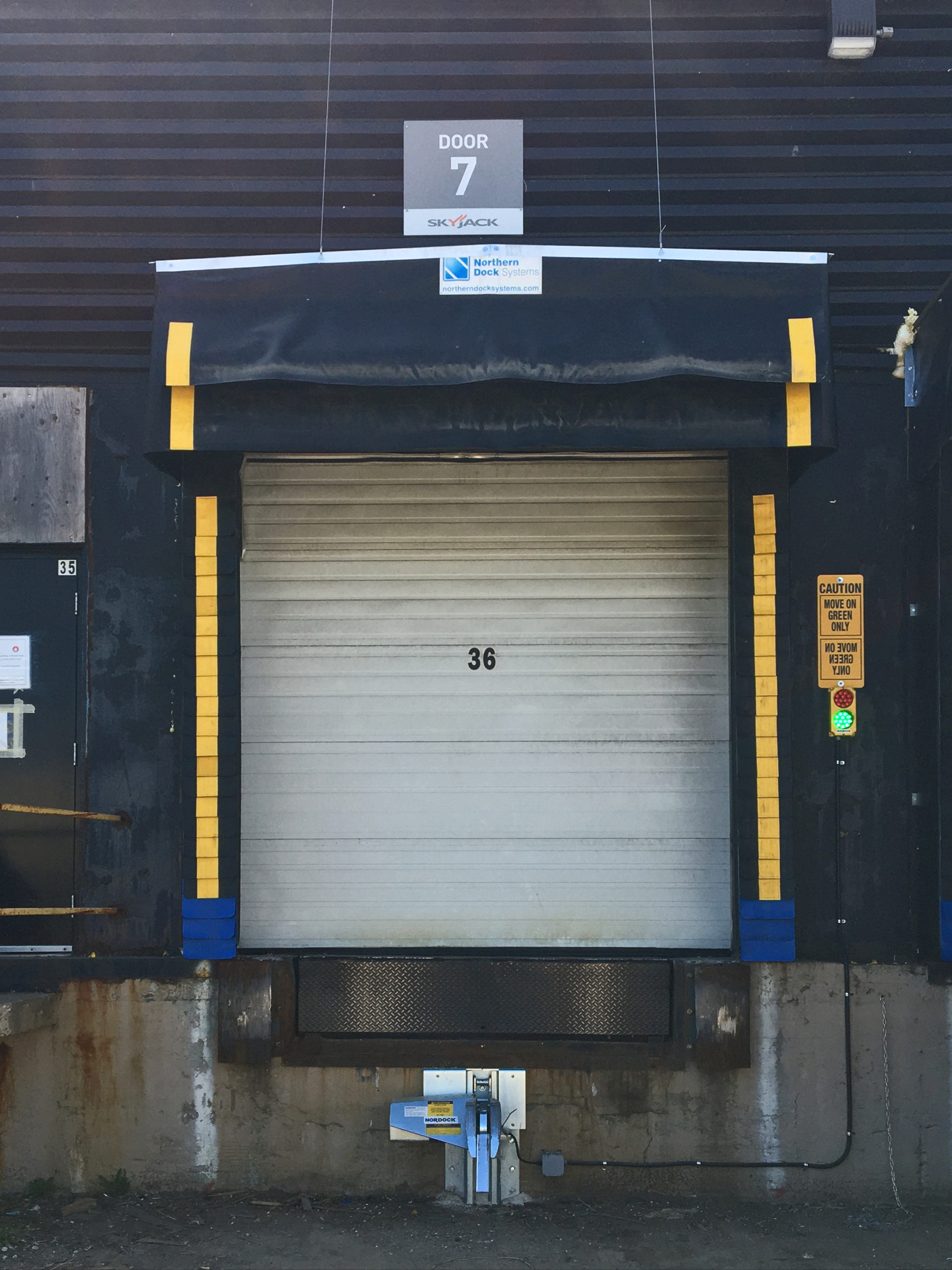 Dock seal with rain deflector and trailer restraint
