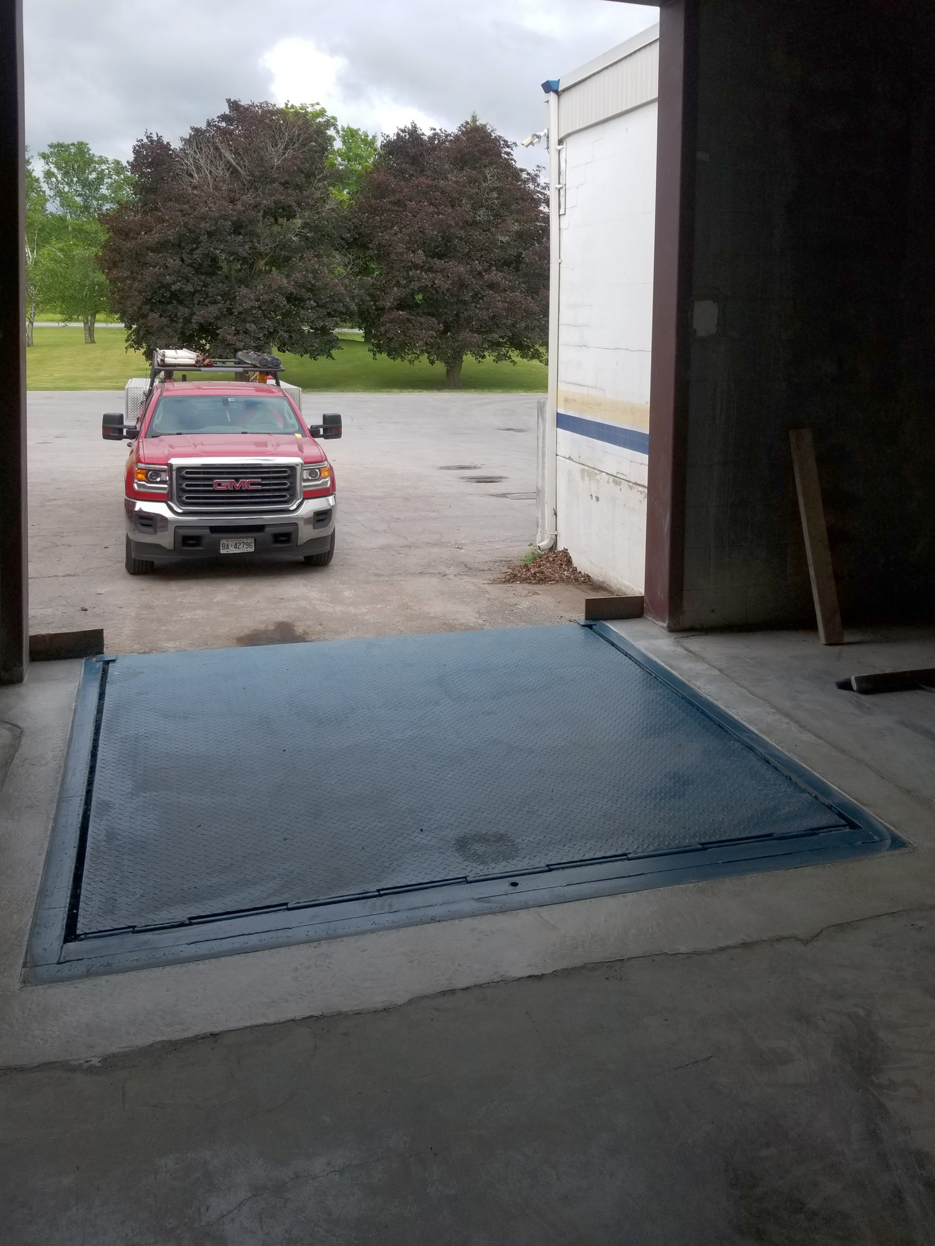 Newly poured cement and dock leveler from inside with truck outside