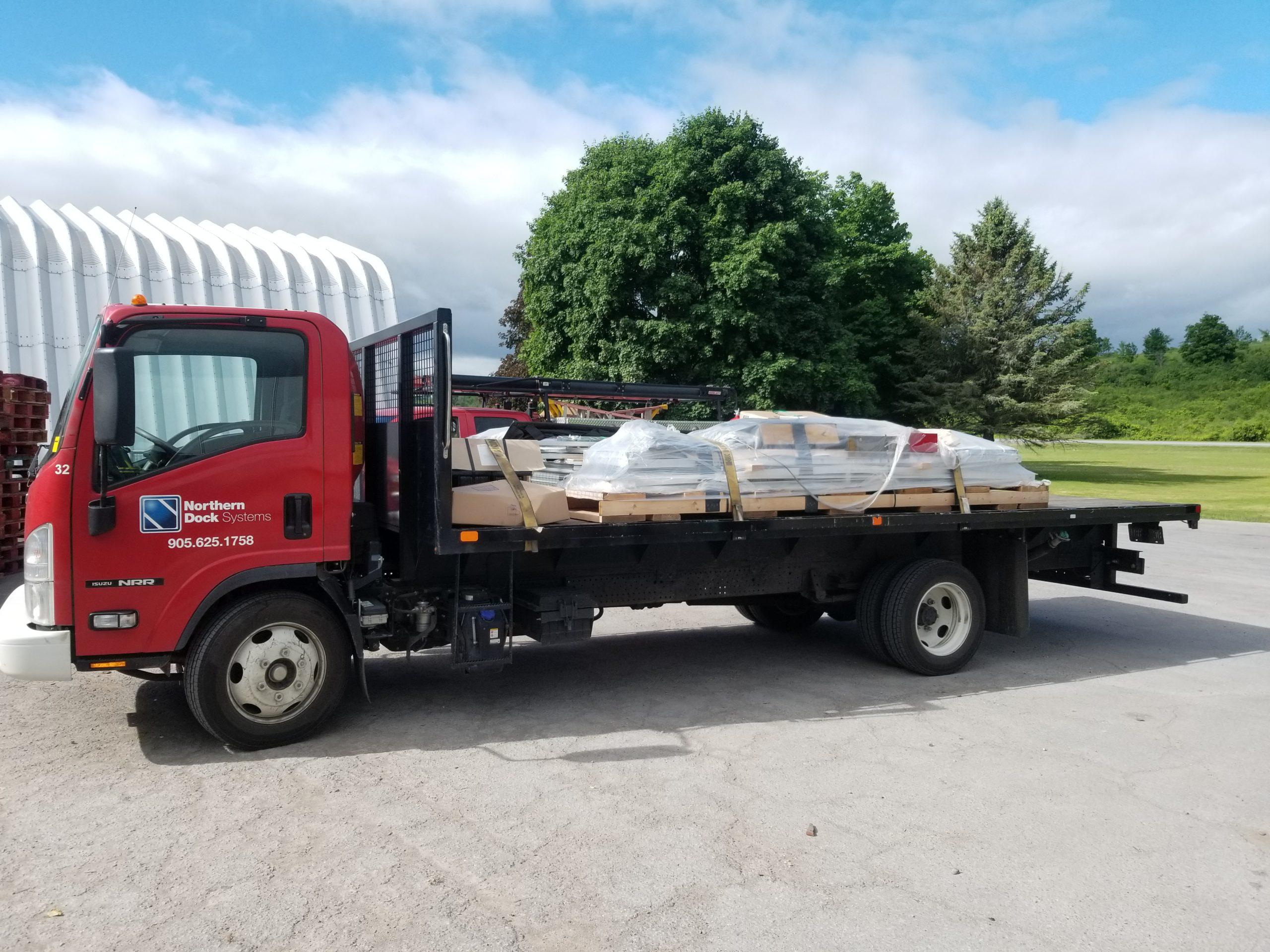 Flatbed truck with loading dock door equipment