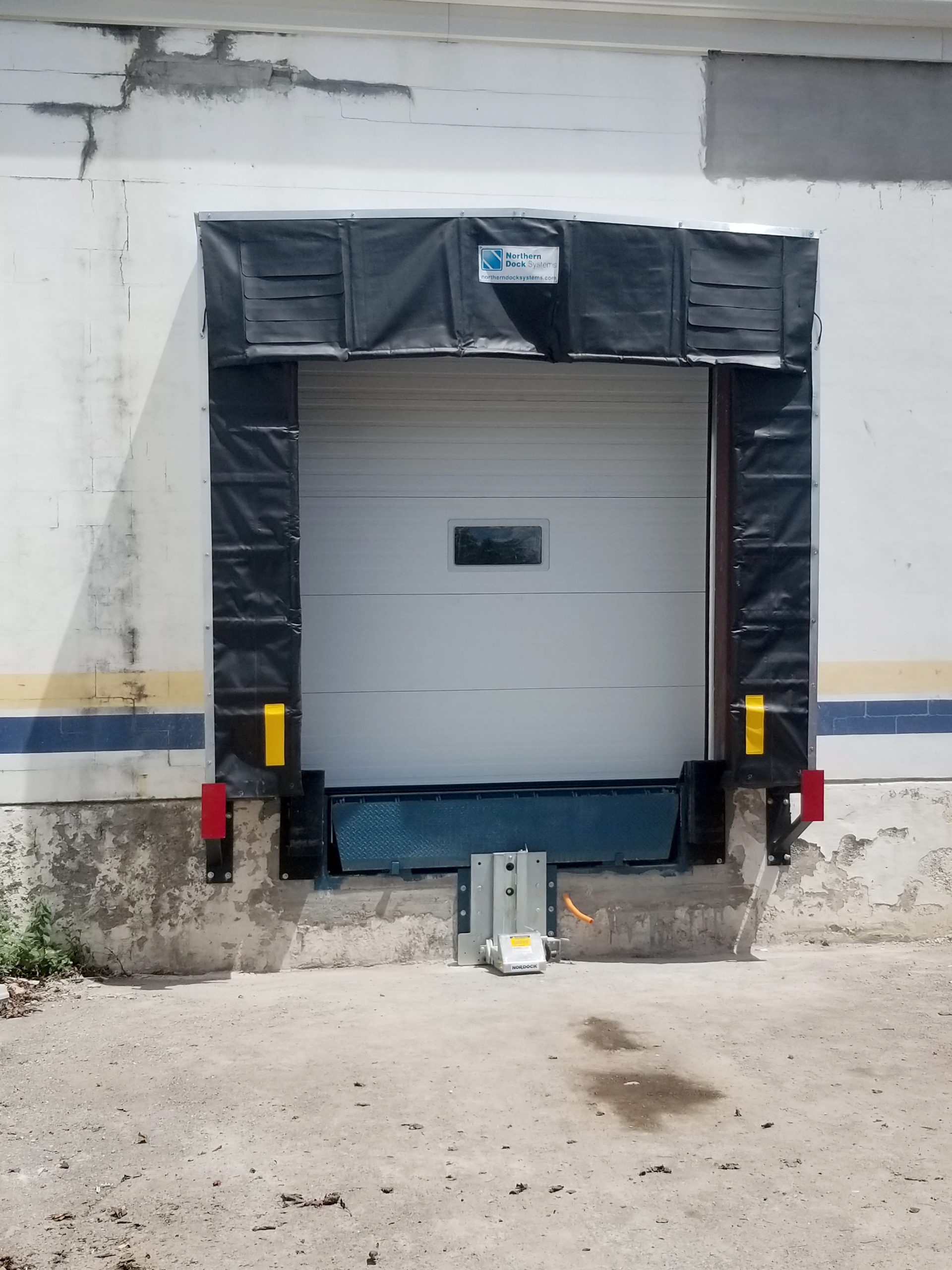 Completed new loading dock position from outside with dock shelter, restraint and bumpers